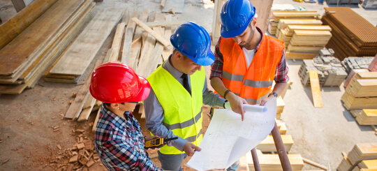 three construction workers holding construction plan