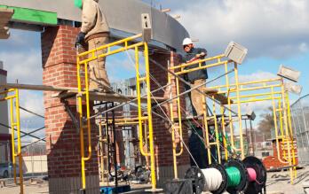 Construction electricians wiring radius atop brick columns