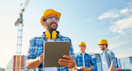 smiling builder holding a tablet